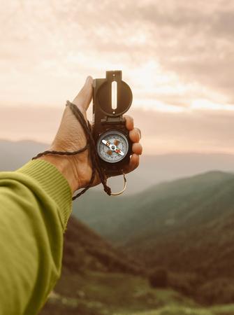 Esploratore viaggiatore maschio che cerca direzione con bussola in montagne estive, punto di vista.