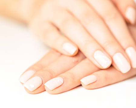 Female hands with smooth skin and stylish beige pastel manicure. Reklamní fotografie - 122196623