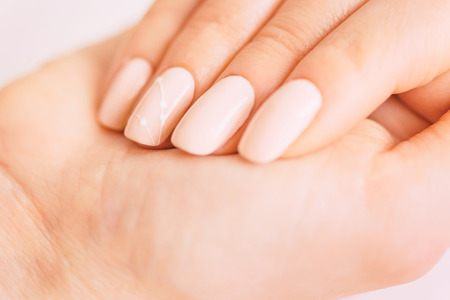 Female hand with professional manicure of beige natural color and art design. Concept of beauty salon. Banco de Imagens - 122196816