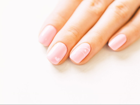 Woman's hand with professional manicure of pink color and art design. Concept of beauty salon.
