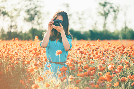 Brunette young woman photographing with a camera in poppy flower meadow in spring outdoor.