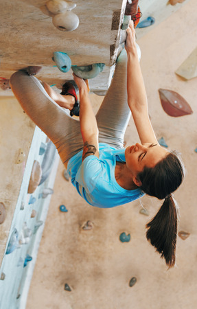 Sporty young woman free climbing on artificial rock wall indoor, bouldering.
