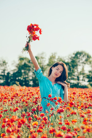 Beautiful young woman wearing in blue dress walking with bouquet in red poppy meadow.