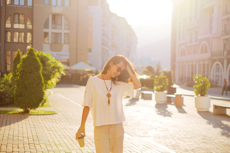 Happy beautiful young woman walking with paper cup of coffee in city in summer morning.