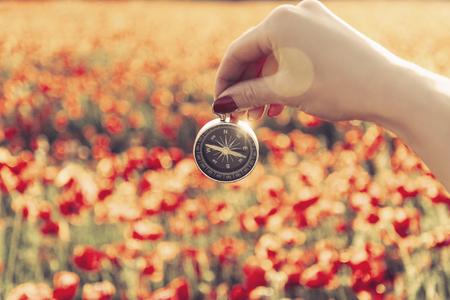 Sicht der weiblichen Hand, die Reisekompass vor roter Mohnblumenwiese im Sommer im Freien hält.