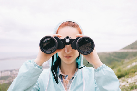 Explorer hiker young woman looking through binoculars on background of summer mountains outdoor, front view. Travel and journey concept.