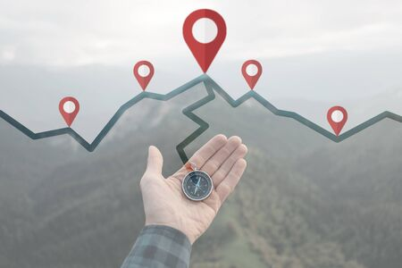 Male hand with compass and connected location pins on background of summer mountains, point of view. Navigation concept. Archivio Fotografico