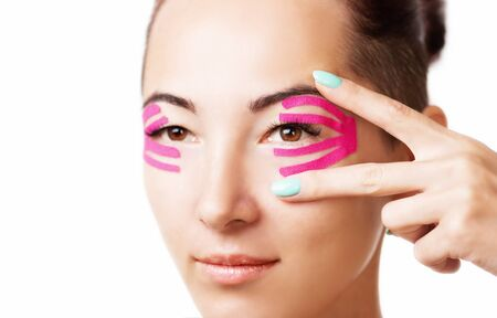 Beautiful young woman with kinesiology tape on eyelid, facelift beauty procedure.