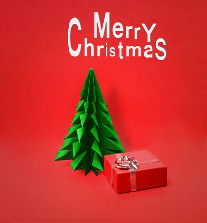 Christmas tree made of origami paper with Gift Box on a red background Stockfoto