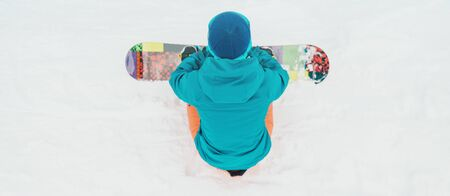 Unrecognizable young woman sitting with snowboard on snow, rear view
