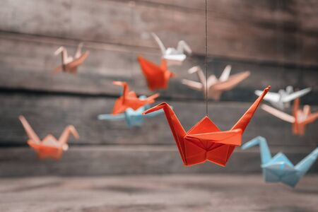 Colorful many origami paper cranes on wooden background 免版税图像