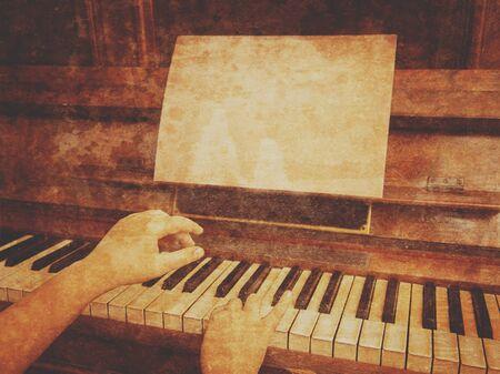 El niño juega en el piano retro, en el espacio en blanco vacío del escritorio para el texto. Imagen de la vendimia