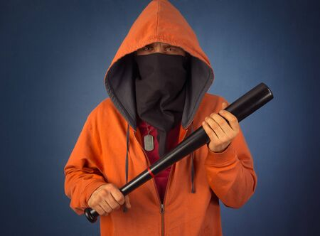 Angry hooligan in the mask and hoody holds baseball bat Imagens
