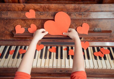 Unrecognizable child holds red paper heart on a background of piano, close-up 写真素材