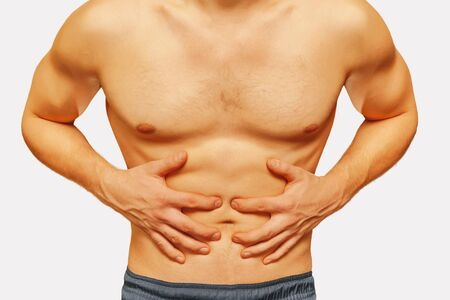 Unrecognizable man compresses the abdomen due to pain on a white background