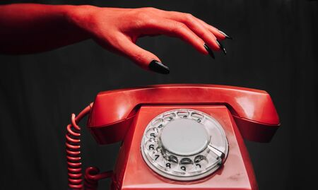 Red devil hand holds a handset of retro phone on dark background. Halloween or horror theme