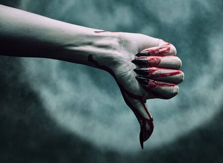 Vampire hand in blood with thumb down gesture on background of full moon. Halloween or horror theme