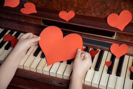 Child holds red paper heart on a background of piano