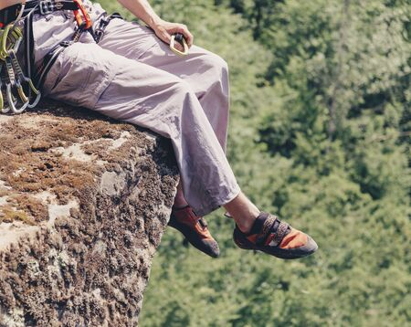 Unrecognizable climber young man with quickdraws sitting on edge of cliff in summer outdoor.