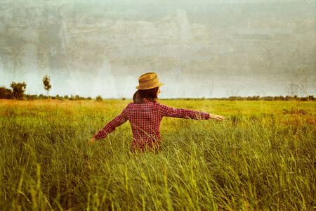 Hipster woman walks in summer meadow and touches green grass, space for text. vintage image