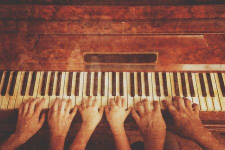 Family of three people is playing the piano, front view. Vintage image