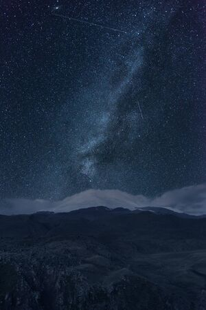 Night sky with stars and milky way over snowy mountains.