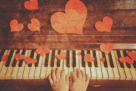 Child is playing on a piano on Valentines Day, side view, face is not visible. Vintage image