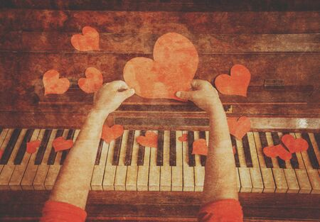 Unrecognizable child holds red paper heart on a background of piano, close-up. Vintage image