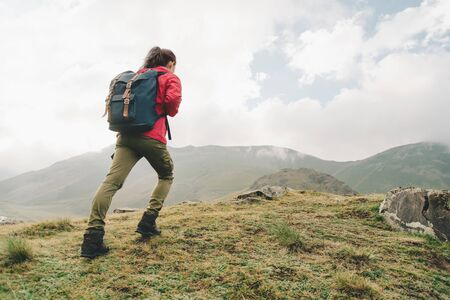 Explorer young woman with backpack going up on hill outdoor.