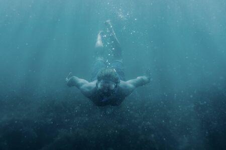 Aktiver männlicher Freitaucher in Maske, der unter Wasser schwimmt, Vorderansicht.
