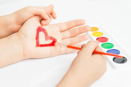 Child paints red heart on the hand, face is not visible