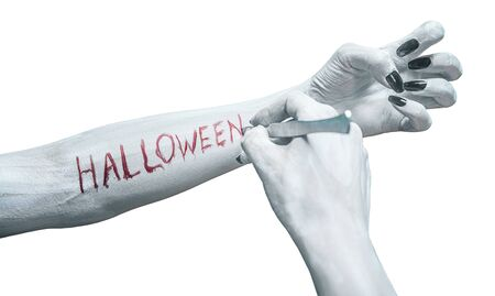 Unrecognizable dead woman writes the word halloween by scalpel on her arm, view of human arms