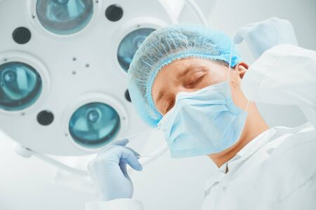Tired man surgeon takes off his protective mask after operation
