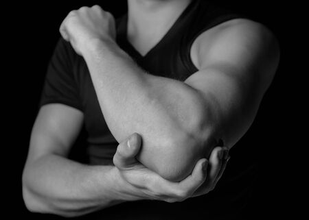 Man holds his the elbow joint, acute pain in the elbow, black and white image