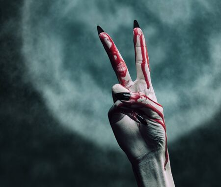 Vampire hand in blood on background of full moon, peace hand sign. Halloween or horror theme