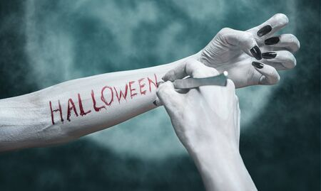 Unrecognizable dead woman writes the word Halloween by scalpel on her arm on background of full moon. View of human arms. Halloween or horror theme
