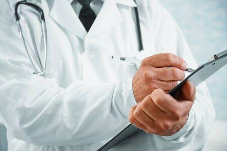 Unrecognizable senior man doctor writes medical records on clipboard