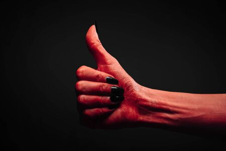 Red demon or devil hand with thumb up gesture on dark background. Halloween or horror theme