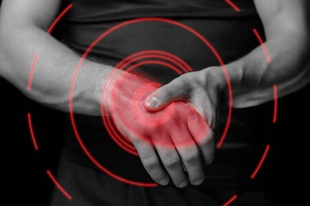 Pain in a male wrist. Man holds his hand, monochrome  image, pain area of red color
