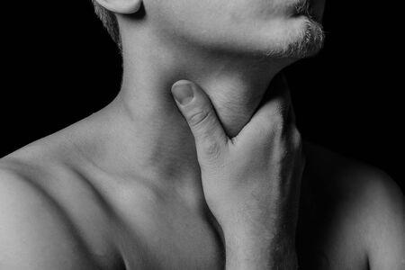 Man touches the throat, sore throat, black and white image