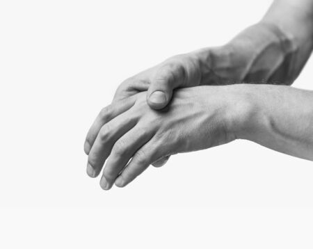 Pain in a male hand. Man holds his hand. Monochrome image, isolated on a white background Reklamní fotografie