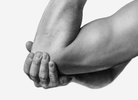 The man is touching the elbow due to acute pain. Monochrome image, isolated on a white background Reklamní fotografie
