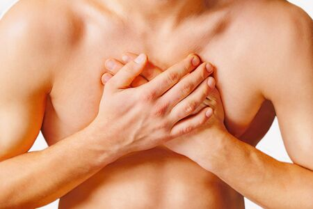 Man is clutching his chest, acute pain possible heart attack. On a white background