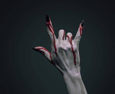 Vampire hand in blood on dark background, rock hand sign Imagens