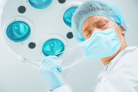 Male surgeon doctor with closed eyes takes off his protective mask after operation