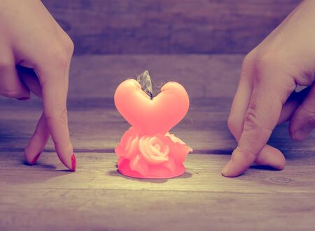 Male and female hands go to burn down candle, concept of broken love