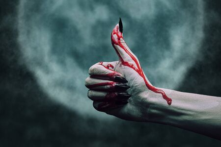 Vampire hand in blood with thumb up gesture on background of full moon. Halloween or horror theme Imagens