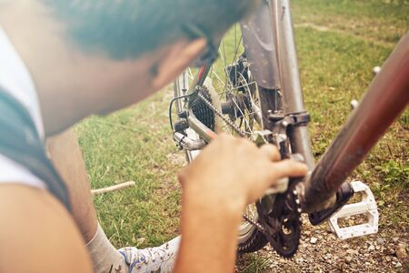 Close-up image of cyclist man checks chain of bicycle in summer park Foto de archivo
