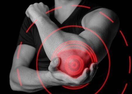 Man houdt zijn ellebooggewricht vast, acute pijn in de elleboog, zwart-wit beeld, pijngebied van rode kleur Stockfoto