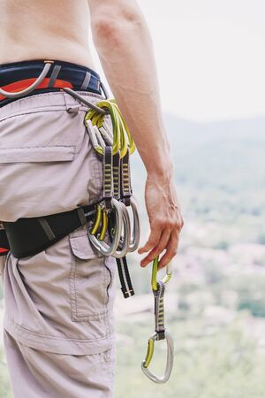 Unrecognizable man climber wearing in safety harness with quickdraws standing in summer outdoor.
